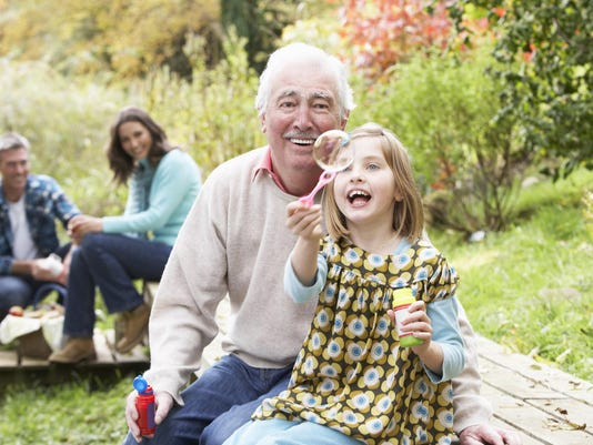 Granddad and granddaughter blowing bubbles on family picnic