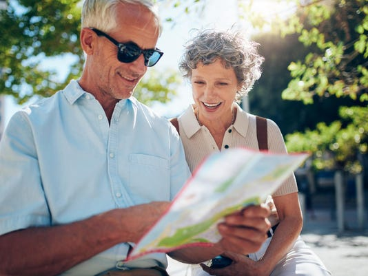 Elderly couple sitting on a bench and using city map