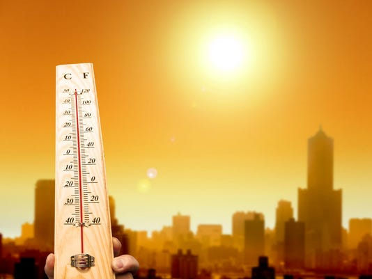 heat wave in the city and hand showing thermometer