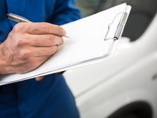 Close up of mechanic writing on clipboard