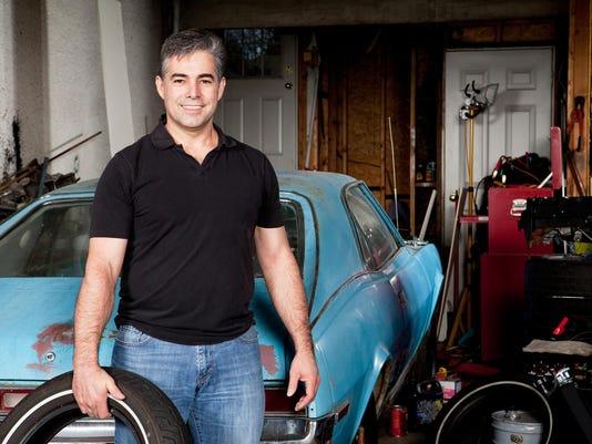 Man standing in his messy home garage holding a tire