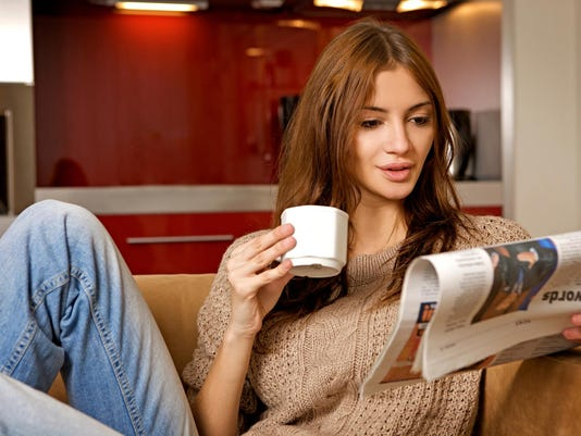 woman drinking coffee and reading news