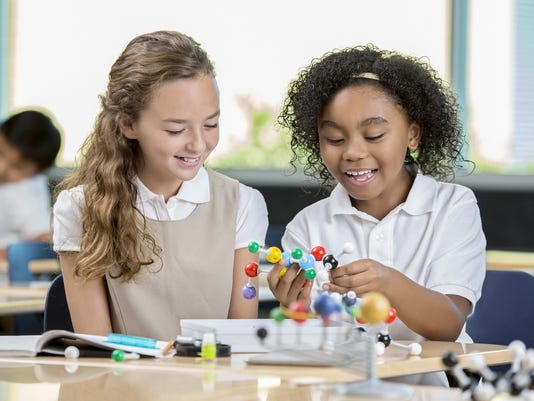 Young girls in science class looking at molecule models
