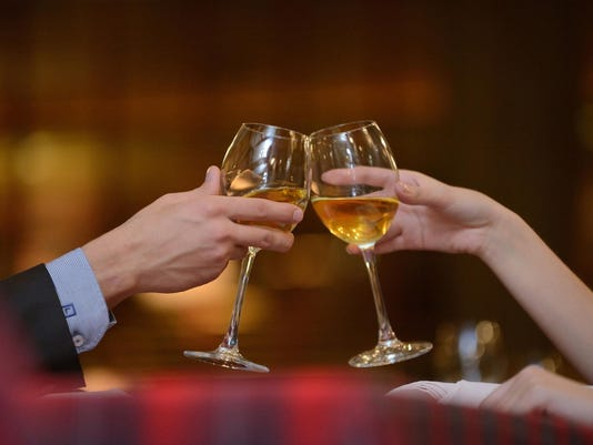Cheers! Two hands hold glasses with white vine