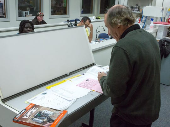 Burlington Technical Center instructor Mitch Stern works at a drafting table during his electricity class.