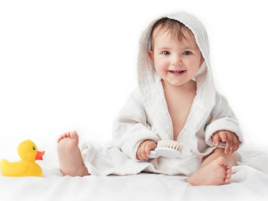 Little baby smiling under a white towel, bath time concept