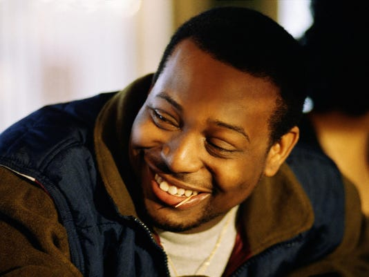 Portrait of a man with a toothpick in his mouth smiling to someone beside him.