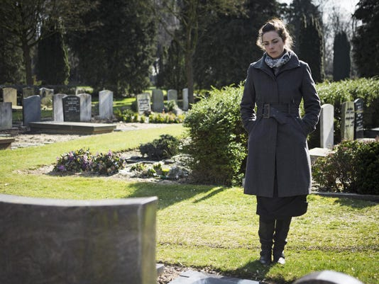 Woman standing at grave
