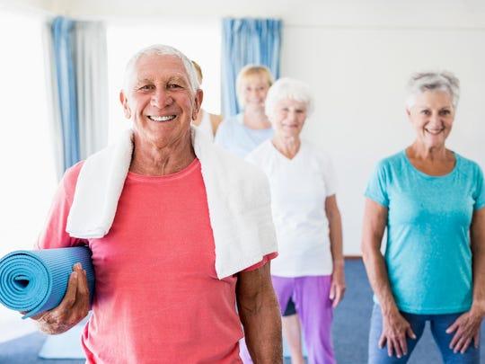 Senior man holding yoga mat