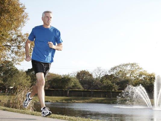 Mature man wearing shorts jogging past water fountain