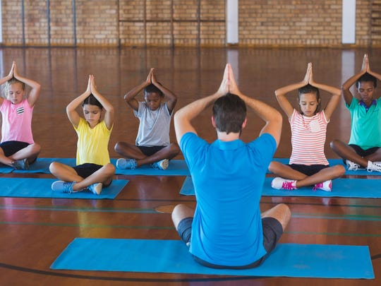 School kids and teacher meditating during yoga class