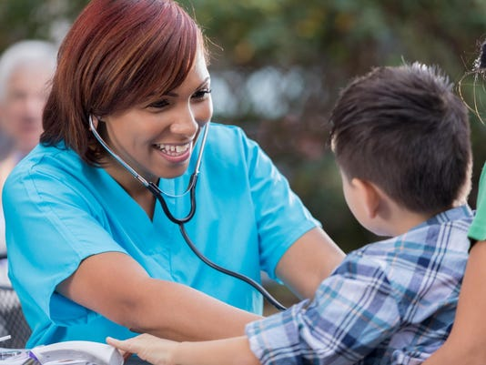 Cheerful nurse checks boys heartbeat at free outdoor clinic