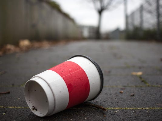Used Coffee mug at sidwalk as symbol for pollution.
