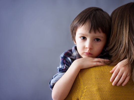 Sad little child, boy, hugging his mother at home