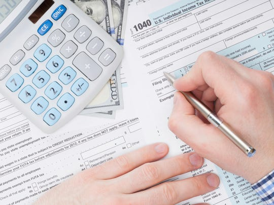 Person filling out tax forms.
