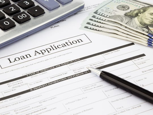 Loan application with pen, calculator, and money