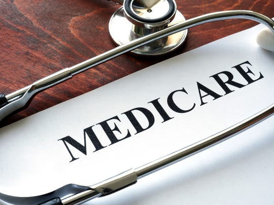 "Paper labeled ""Medicare"" with a stethoscope on top of it, on a wood desk."