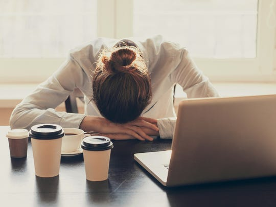A woman surrounded by coffee cups has her head down on a desk