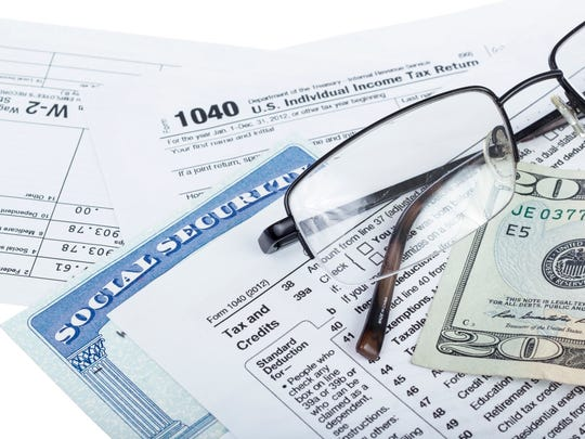 A Social Security card wedged between IRS tax forms, with a pair of glasses and a twenty-dollar bill lying atop the tax forms.