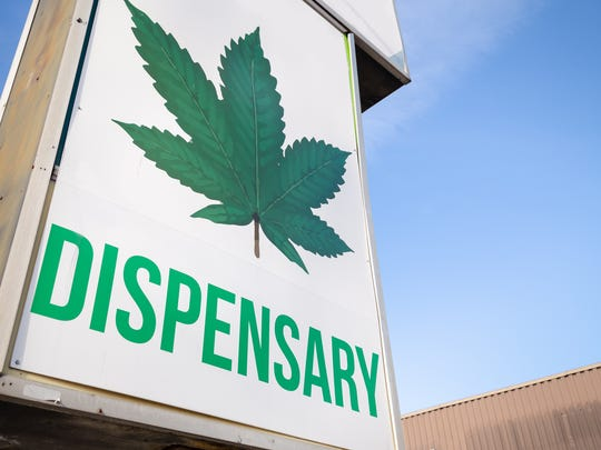 A large dispensary sign with a huge cannabis leaf and the word dispensary underneath it.