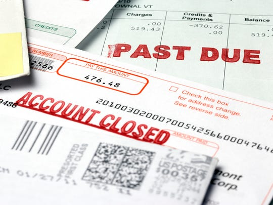 Stack of bills labeled past due and account closed.