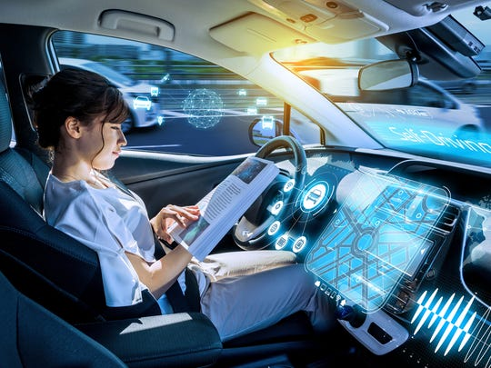 A young woman reads a book as she sits in a driverless car.