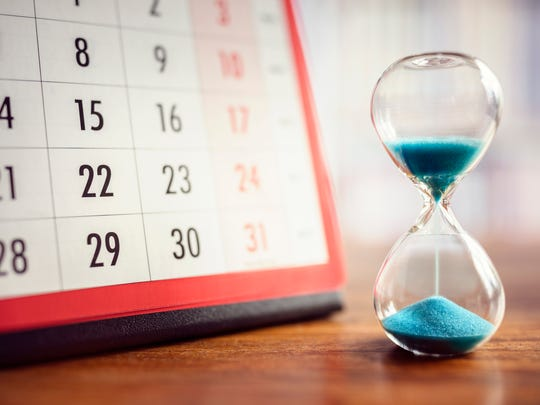 A half-emptied hourglass next to a calendar on a table.