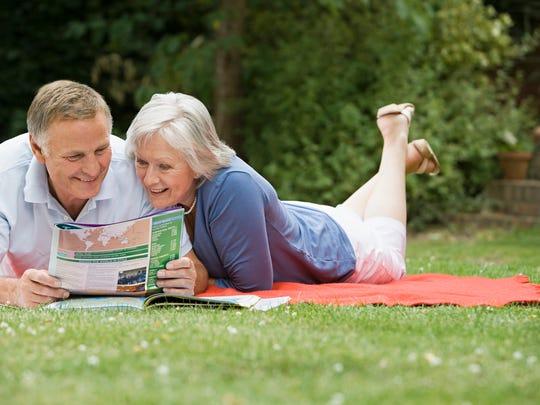 Senior couple lying on blanket on grass reading pamphlet
