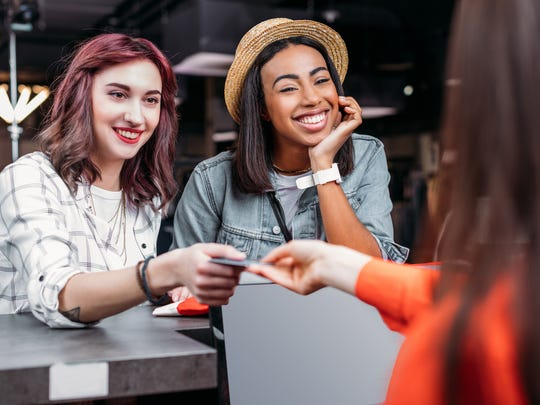 Two young women paying for a purchase with a credit card