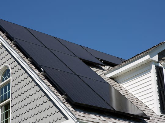 Part of a house's roof is shown, covered with solar panels.
