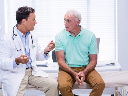 Doctor sitting next to senior man on exam table, talking