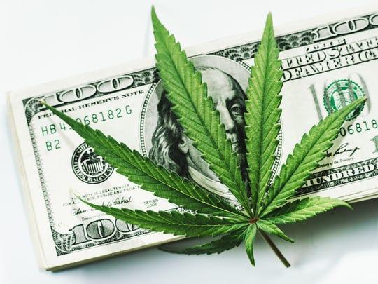 Marijuana leaf on top of pile of $100 bills.