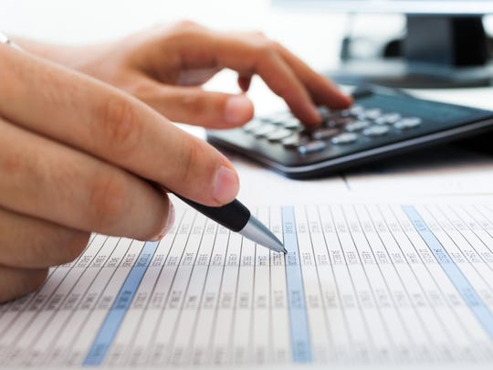 An accountant double-checking figures line by line with the aid of a calculator.
