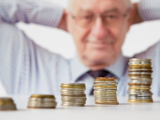 Elderly man with hands behind his head and looking at five more and more stacks of coins
