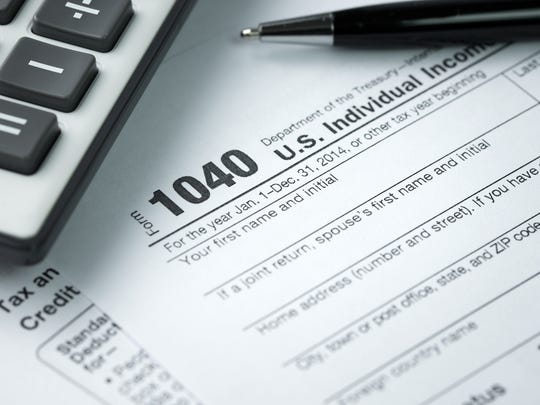 A 1040 IRS tax form with a calculator and pen on top of it.