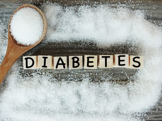 Diabetes word on wooden letters with crystalized white sugar as frame.