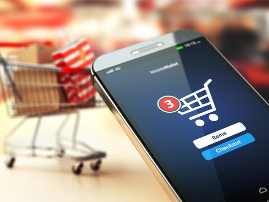 A virtual shopping cart on a smartphone with a real cart in the background.