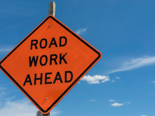 An orange Road Work Ahead sign in front of a blue sky