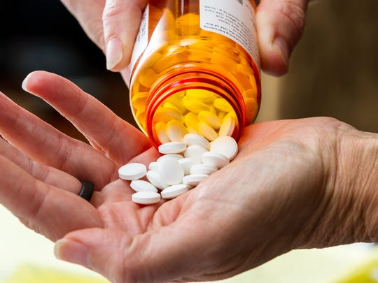 Prescription bottle pouring pills into a hand