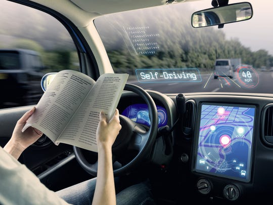 A person reading a book while behind the wheel of a self-driving car that's on the road.
