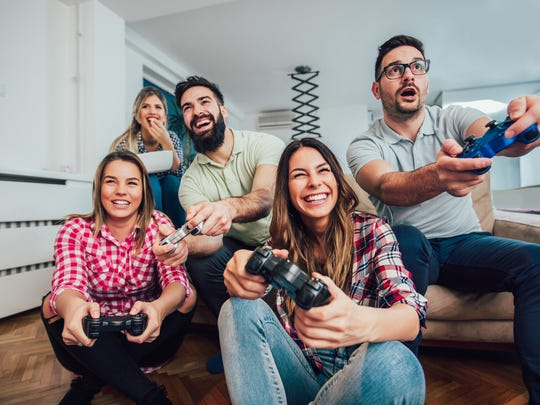 A group of smiling young people playing a video game.