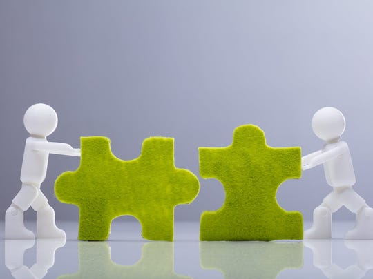 Two figures push together two jigsaw pieces.