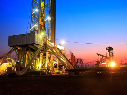 Drilling rigs lit up at dusk.