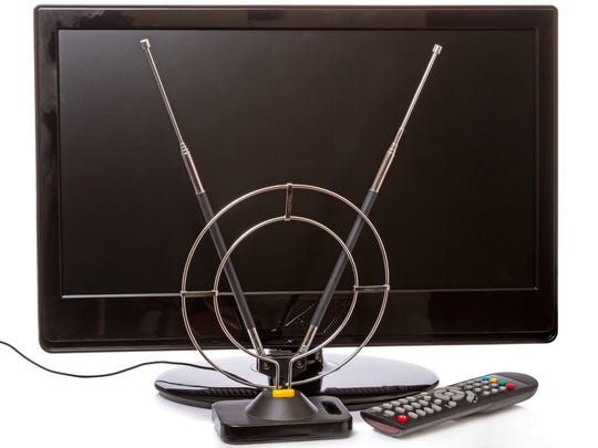 Photograph of OTA rabbit ears antenna in front of a modern flat screen TV