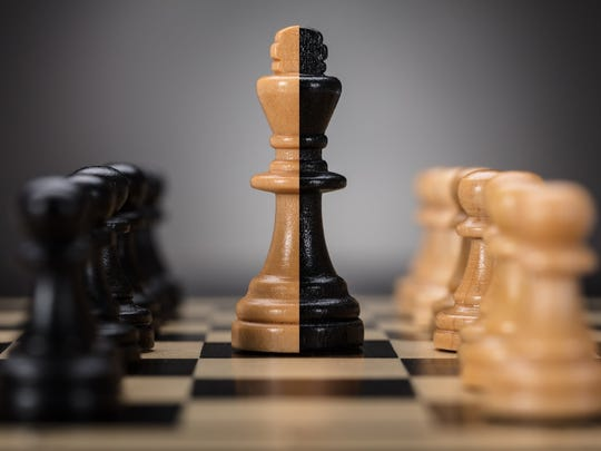 A chess board where a single half-white and half-black king stands between two lines of opposing pawns.