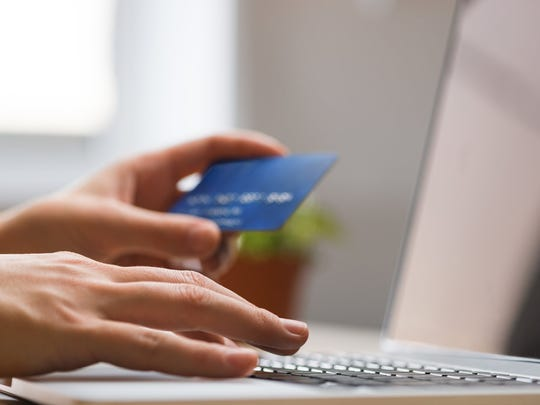 Hands holding credit card, typing on the keyboard of laptop.