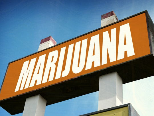 A large cannabis sign that reads, Marijuana, in front of a retail store.