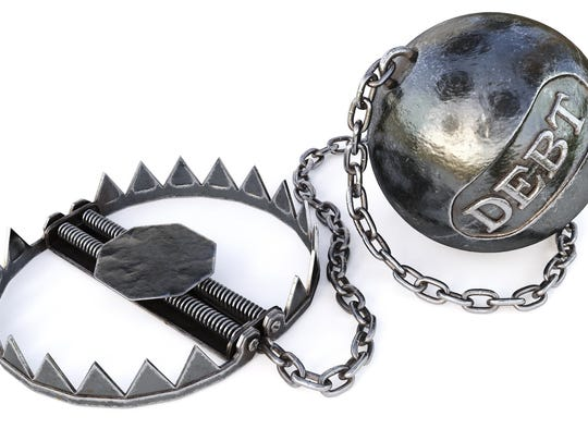 "A weighted ball with the word ""debt"" etched on it, attached by a chain to a bear trap"