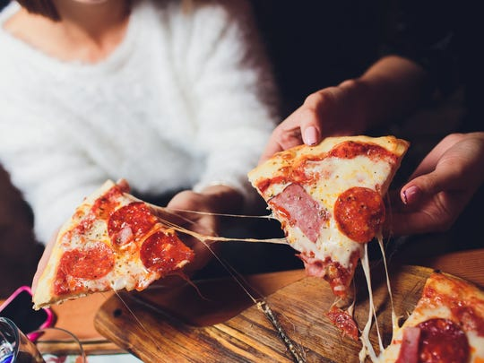 Two people sharing a pizza.