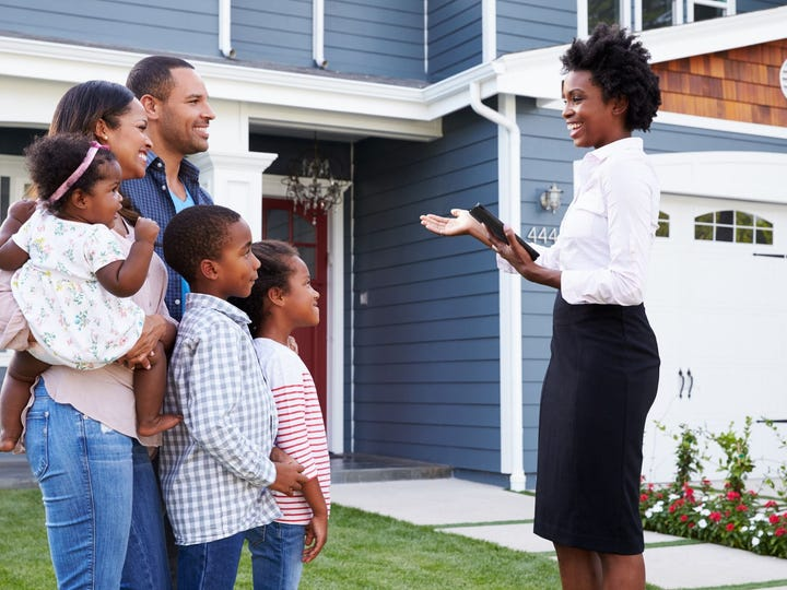 A real estate agent showing a family a house